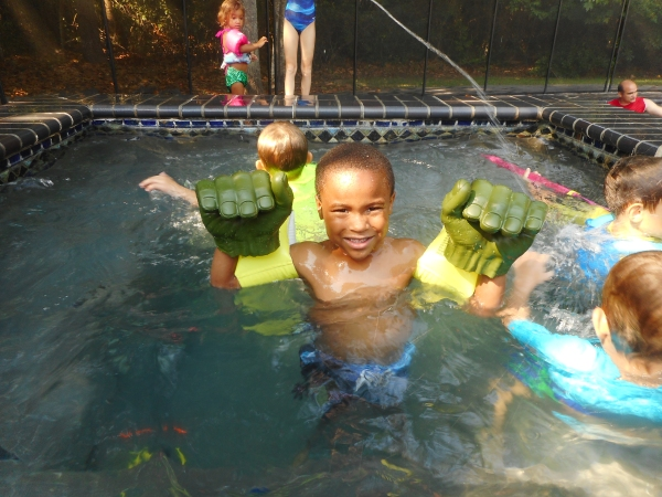 Boy in pool with Hulk Hands